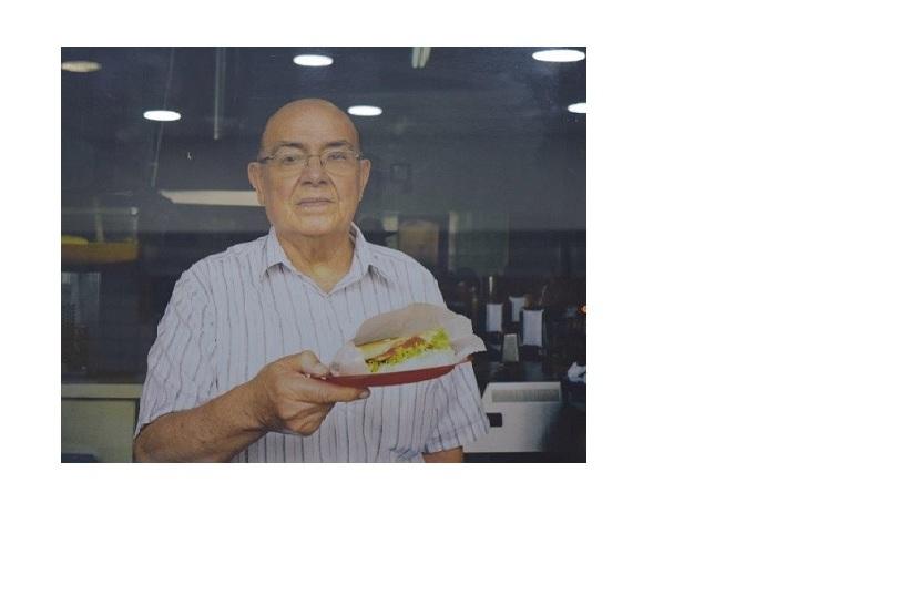 Seu Oswaldo servido um sanduiche em seu restaurante